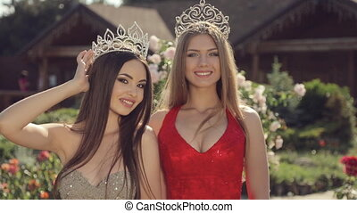 Two gorgeous girls in long gowns and crowns in a garden with...