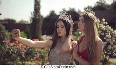 Two girls in evening gowns and crowns make selfie on phone in a garden with roses