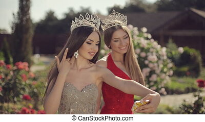 Two beautiful girls in evening gowns and crowns fooled...