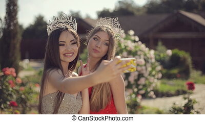 Two charming girls in evening gowns and crowns laughing and...