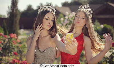 Two attractive girls in beautiful dresses and crowns laughing and doing phone selfie in a garden with roses