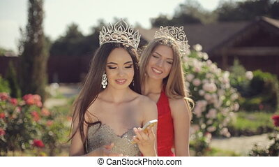 Two sexy young females in beautiful evening gowns and crowns...