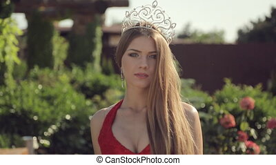 Beautiful girl with a crown and a slender figure walking in...
