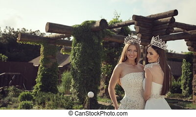 Portrait of two girls in wedding dresses and crowns outdoors...