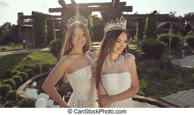 Charming girls in crown and white wedding dress posing and...