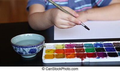 Little boy paints