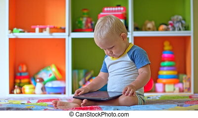 Toddler boy plays with tablet compu