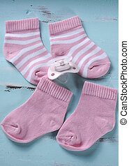 Baby girl nursery pink and white stripe socks and pacifier dummy on vintage aqua shabby chic wood