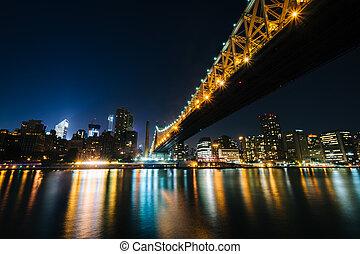 The Queensboro Bridge and Manhattan skyline at night, seen from Roosevelt Island, New York.
