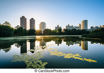 Sunrise over buildings and the Harlem Meer, in Manhattan,...
