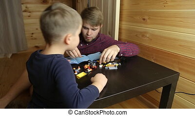 Boy playing with lego cubes - Father and son playing with...
