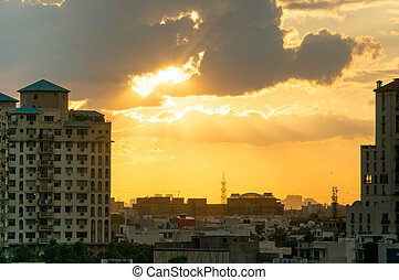 Gurgaon apartments at sunset with light rays passing through...
