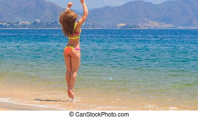 blonde girl in bikini jumps swings in shallow water on beach