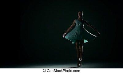 girl dances in a pretty blue dress on a dark background