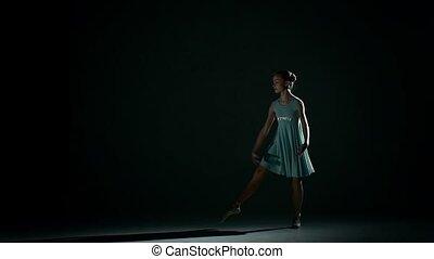 ballerinan in  pretty blue dress on a dark background