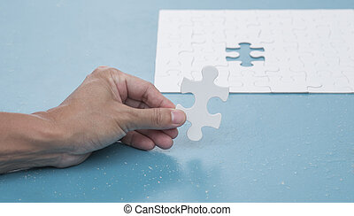 Man hand holding jigsaw puzzle