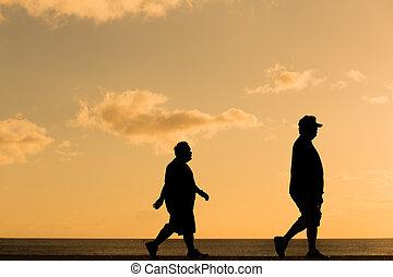 Silhouette fat man walking at sunset