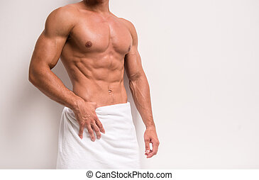 Strong man - Young shirtless man covered with towel standing...