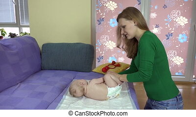 Woman exercise baby - Woman exercise little baby on sofa at...