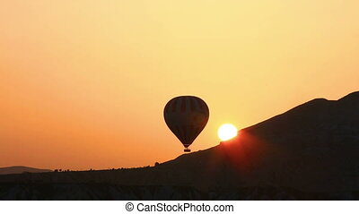 Silhouette of balloon over hill at sunset - Balloon...