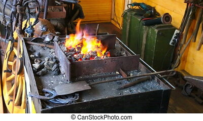 Bright flame and tools in a forge - View at forge shop with...
