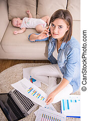Mom and kid - Young woman is working at home while her...