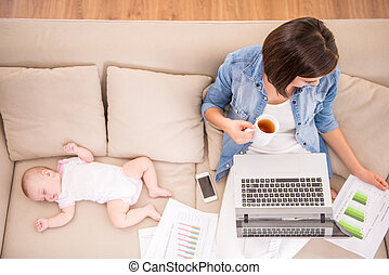 Mom and kid - Top view of young woman is working at home and...