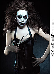 Young woman in the image of evil gothic freak clown with...