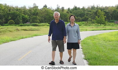 Asian senior couple walking nature - Video of happy Asian...