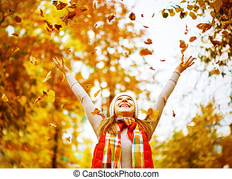 Happy girl throws up autumn leaves in park for walk outdoors