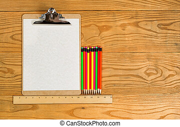 Blank clipboard with paper and colorful pencils on desktop -...