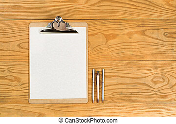 Blank clipboard with paper and pens on desktop - Top view of...