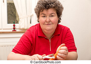 mentally disabled woman is peeling carrots