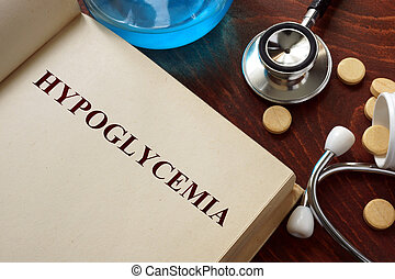 Hypoglycemia written on book with tablets. Medicine concept....