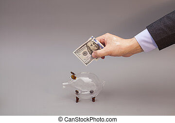 Male hand putting one hundred dollars bill into glass piggy bank isolated on gray