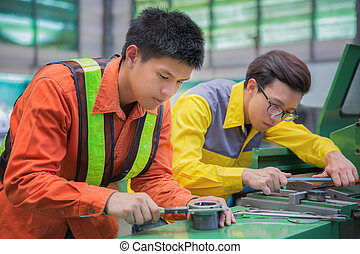 male technician machinist worker adjusting and repair machine