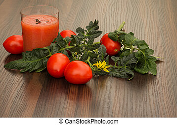 glass of tomato juice and tomato with leaves