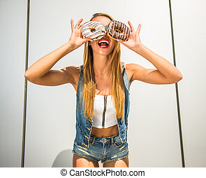Playful woman - Playful young woman holding donuts against...