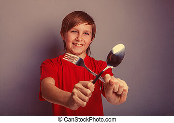 Teenager boy in red shirt twelve years holding a spoon and...