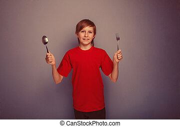 Teenager boy twelve years in a red shirt holding a spoon and...