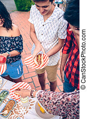Young man holding hot dog in a barbecue with friends - Happy...