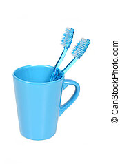dental care - two blue toothbrushes in a blue cup over white...