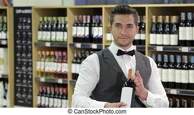 Confident sommelier. Confident male sommelier holding wine...