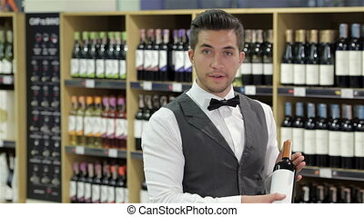 Presenting a wine bottle Smiling young sommelier standing in...