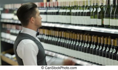 Choosing the right wine. Confident male sommelier examining...