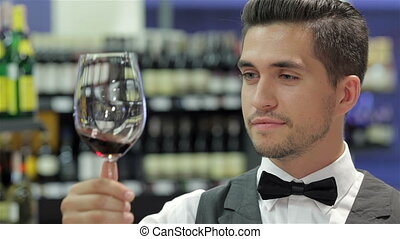 This wine is perfect. Confident male sommelier examining...