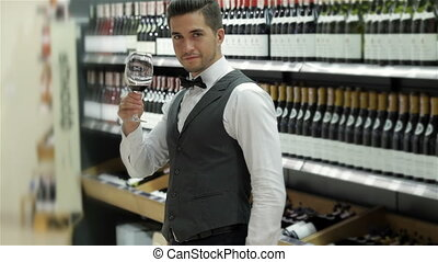 Testing wine. Confident male sommelier testing wine while...