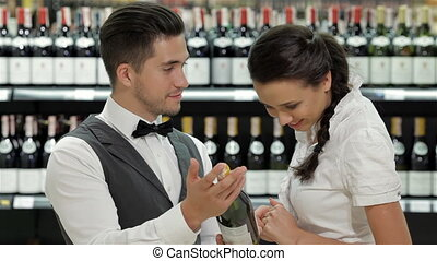 Salesman in supermarket offering bottle of red wine to...