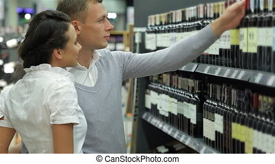 Couple selecting wine in supermarket. Choosing wine in a...