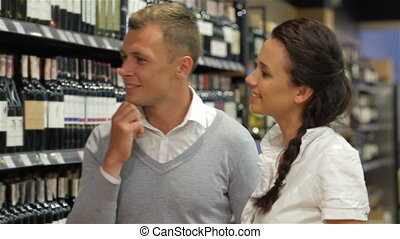 Married couple buying wine and beer in a supermarket.